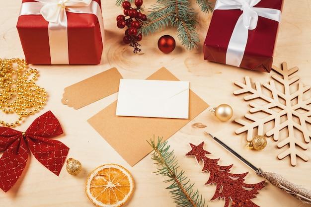 Carta de felicitación, sobre y pluma rodeada de adornos navideños