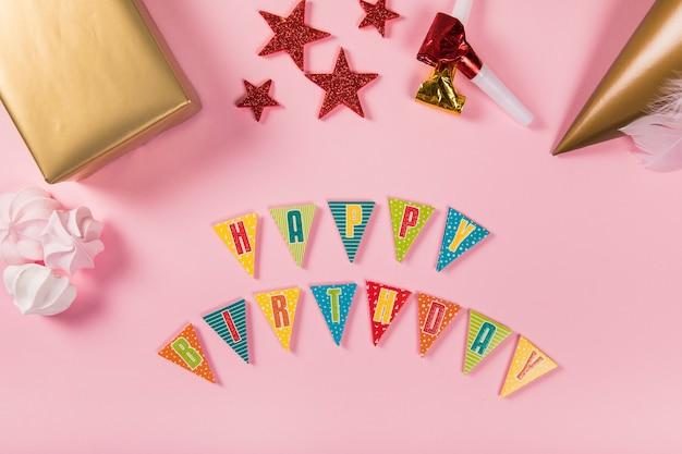 Carta de feliz cumpleaños con artículos de fiesta y zephyrs sobre fondo rosa