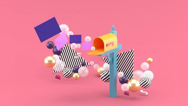 Una carta flotante de un buzón rodeado de bolas de colores en rosa. representación 3d