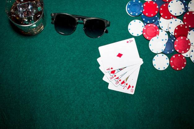 Carta de juego; fichas de casino; gafas de whisky y gafas de sol sobre fondo verde de póquer