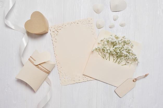 Carta de la maqueta con un bolígrafo y una caja de regalo para tarjetas de felicitación día de san valentín en estilo rústico