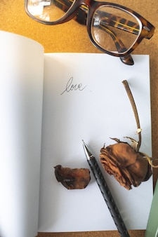 Carta de palabra de amor en el libro blanco con pluma rosa marchita y gafas retro en tablero de corcho