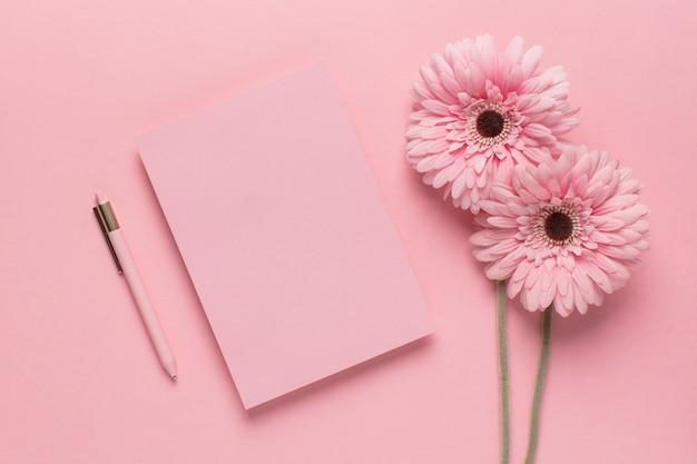 Carta rosa con flores rosas y bolígrafo