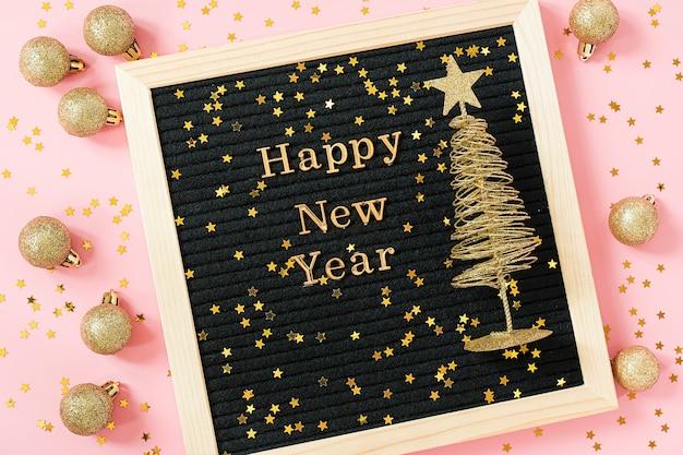 Carta con texto dorado feliz año nuevo y brillante árbol de navidad en rosa