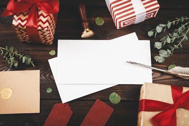 Carta vacía con una pluma sobre fondo de madera vieja decorada con objetos de navidad