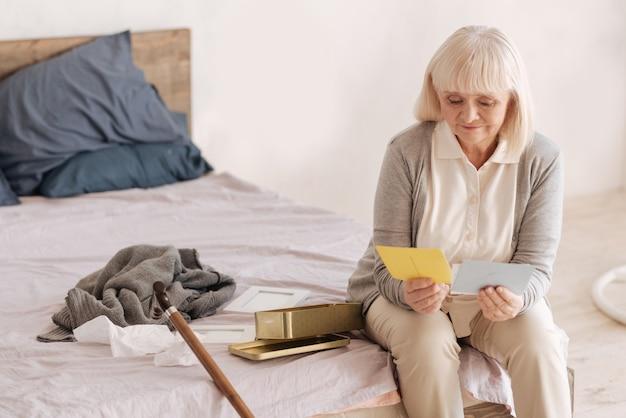 Cartas de amor. agradable y agradable anciana sosteniendo viejas cartas de amor y leyéndolas mientras piensa en su juventud