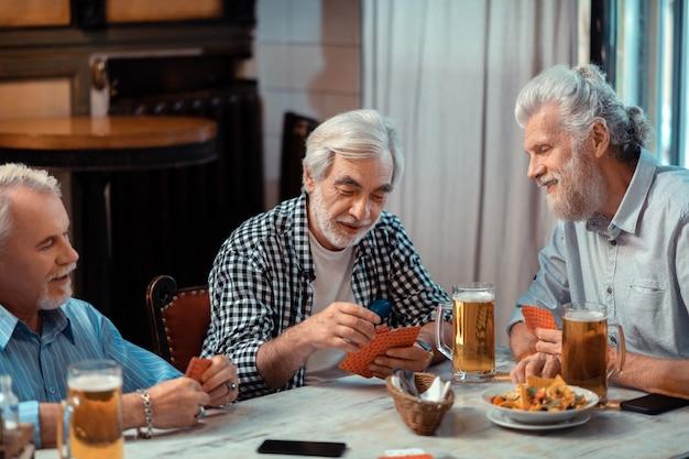 Cartas y cerveza. tres jubilados jugando a las cartas mientras beben cerveza en el pub juntos