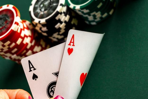 Cartas y fichas para póker en mesa verde.