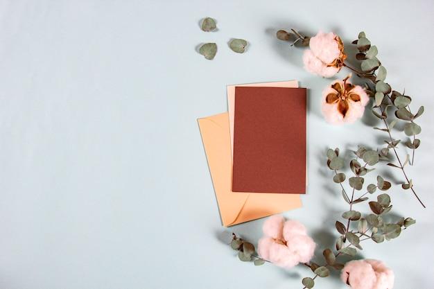Cartas de invitación con hojas de eucalipto y flores de algodón sobre fondo claro