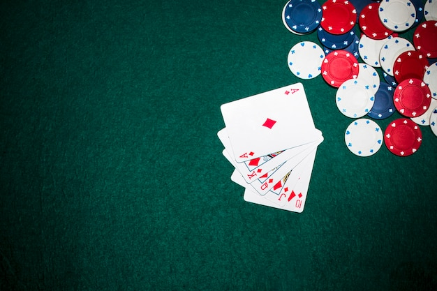 Cartas de juego de escalera real y fichas de casino en el fondo de póquer verde