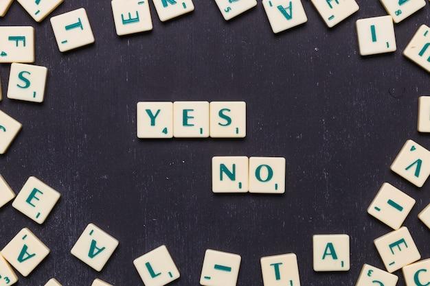Cartas sí o no hechas de cartas del juego scrabble contra fondo negro