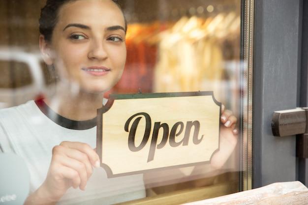 Cartel abierto en el cristal de la cafetería o restaurante de la calle