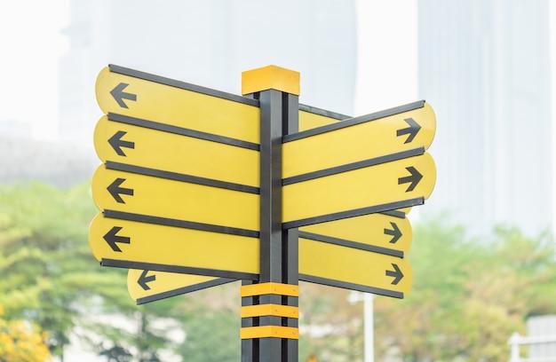 Cartel amarillo con flechas en la carretera en la gran ciudad