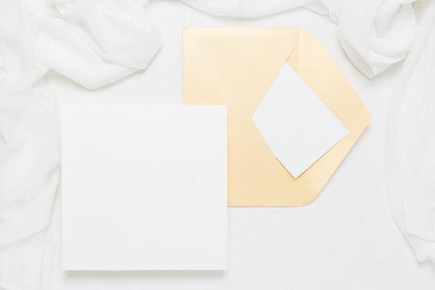 Cartel blanco cerca de sobre amarillo con bufanda sobre fondo blanco