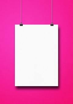 Cartel blanco colgado en una pared rosa con clips