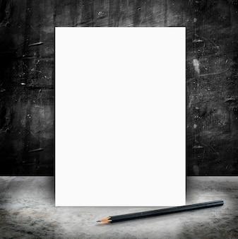 Cartel blanco en blanco y lápiz en un piso de concreto brillante y pared de cemento negro grunge