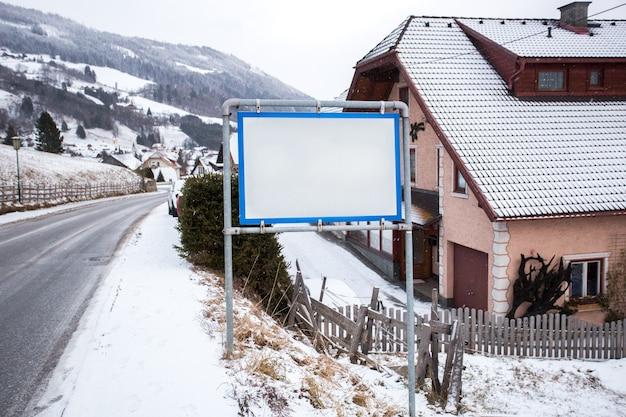 Cartel blanco con espacio de copia en aldea austriaca en las montañas