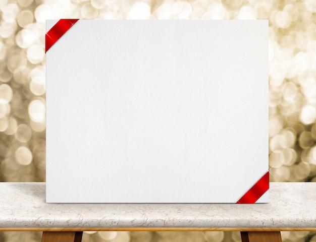 Cartel en blanco de papel blanco o lienzo con cinta roja en la mesa de mármol y luz dorada brillante de bokeh