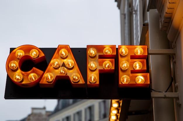 El cartel de bombillas con la palabra cafe en la calle de la ciudad.