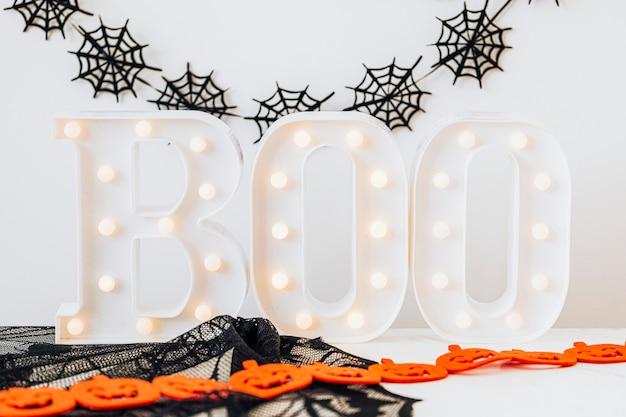 Cartel de boo iluminado sobre una mesa blanca con decoración de halloween