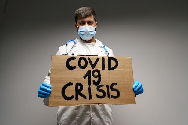 Cartel de 'covid-19 crisis' en manos del médico manifestante sobre fondo gris.