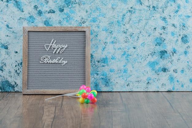 Cartel de feliz cumpleaños incrustado sobre fondo gris