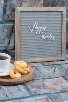 Cartel de feliz lunes con una taza de bebida y galletas alrededor