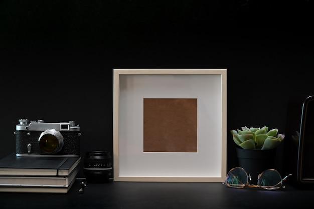 Cartel de foto de marco de maqueta con libros y cámara vintage en mesa oscura