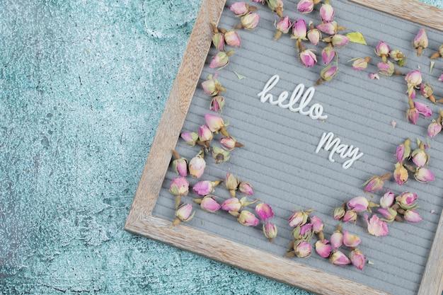 Cartel de hola mayo incrustado sobre fondo gris con flores alrededor