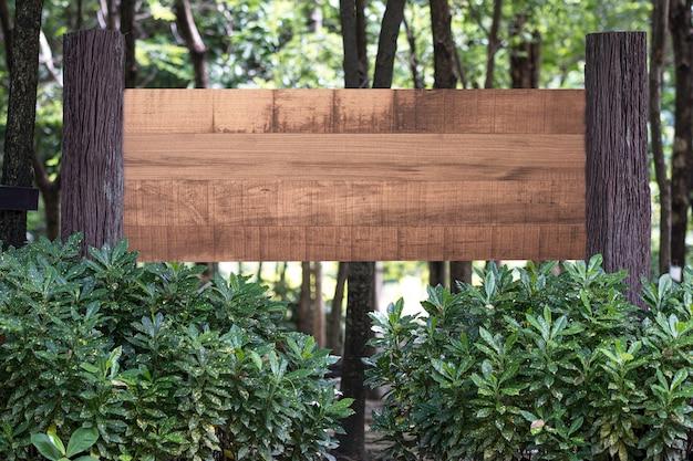 Cartel de madera en blanco en el bosque con concepto de espacio de copia.