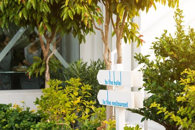 Cartel de madera en el jardín que muestra el camino hacia el hotel y el restaurante.