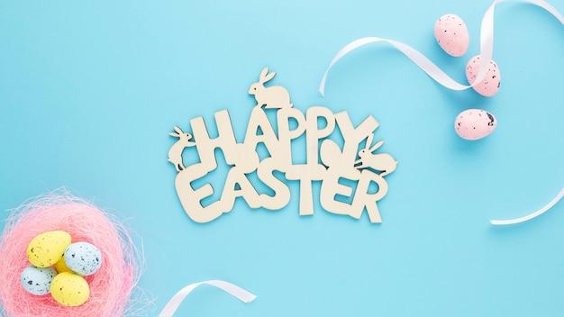 Cartel de madera de pascua feliz con huevos sobre un fondo azul.