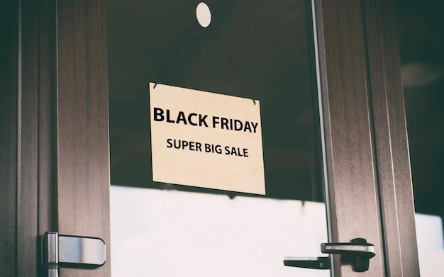 El cartel de madera con texto black friday sale colgando de la puerta de la tienda