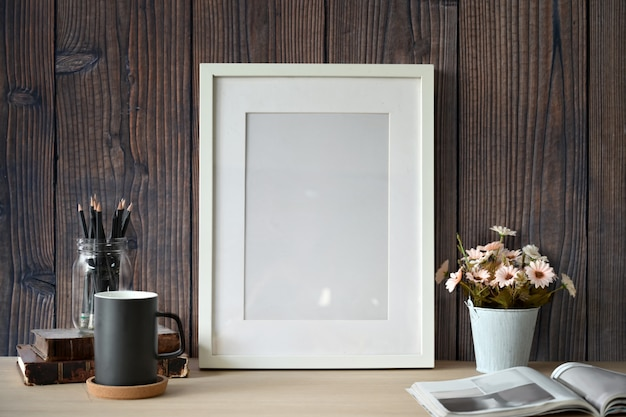 Cartel de maqueta blanca con suministros de oficina en casa sobre pared de madera.