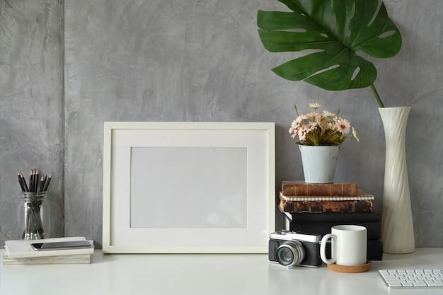 Cartel de marco de maqueta en blanco en el espacio de trabajo de hipster