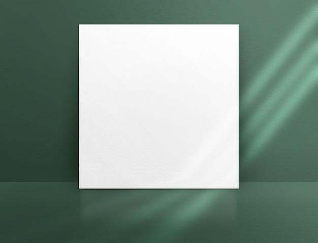 Cartel de papel blanco en blanco apoyado en un muro de concreto de color verde y piso con luz solar de ventana