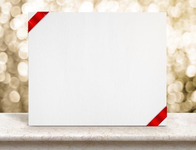 Cartel de papel blanco en blanco con cinta roja en la mesa de mármol