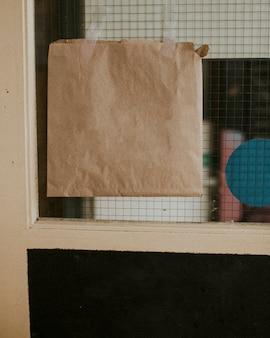 Cartel de papel en blanco colgado en un escaparate cerrado