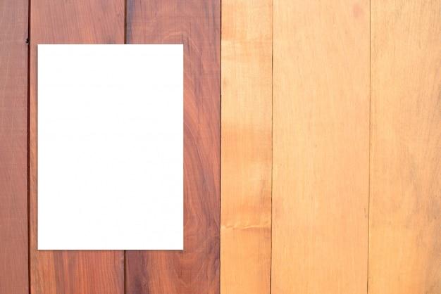 Cartel de papel doblado en blanco colgado en pared de madera