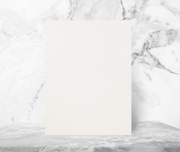 Cartel de papel con textura eco en blanco sobre la mesa de piedra de mármol en el fondo de la pared de mármol blanco.