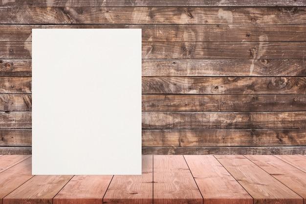 Cartel de papel textured en blanco de eco en la sobremesa de madera en la pared de madera vieja