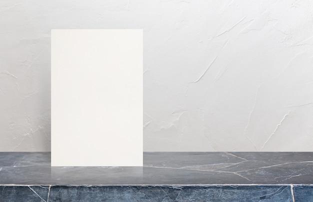 Cartel de papel texturizado eco en blanco en la sobremesa de piedra de mármol en el fondo blanco de la pared.