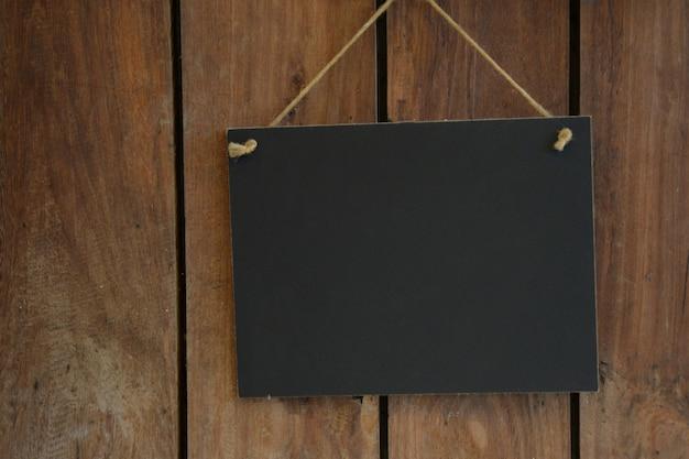 Cartel de pizarra sobre fondo de madera con espacio de copia para publicidad