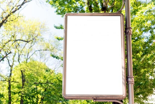 Cartel publicitario vertical de la cartelera de la calle en blanco en fondo del parque de la ciudad.