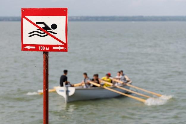 Cartel que prohíbe nadar en este lugar y bote de remos de madera con personas