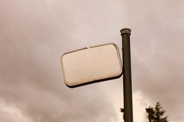 Cartel roto en blanco con un fondo de cielo gris