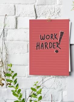 Cartel de trabajo más duro en pared blanca.