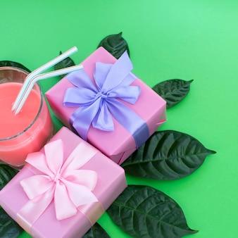 Cartel de vacaciones cajas con regalos un vaso de batido de leche de un fondo verde brillante.