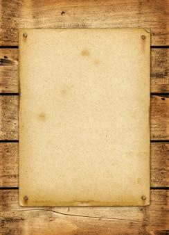 Cartel vintage en blanco clavado en un tablero de madera