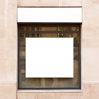 Cartelera blanca en ventana de tienda